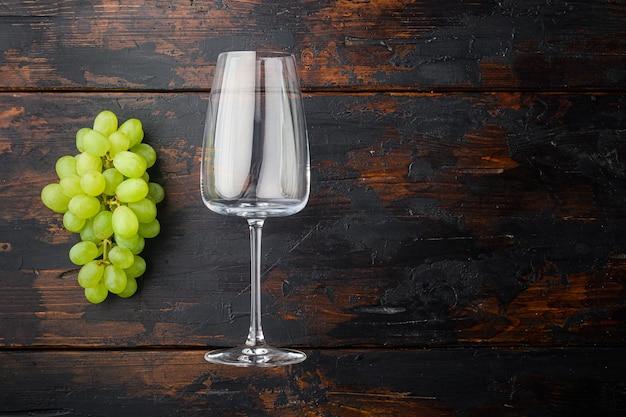Conjunto de copos de vinho com uvas, na velha mesa de madeira escura, vista de cima plana