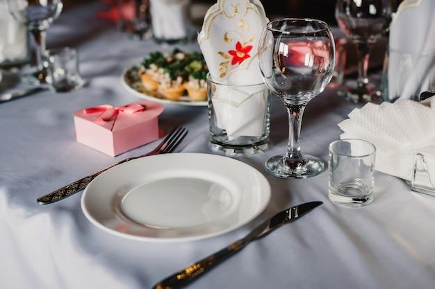 Conjunto de copos e pratos vazios com talheres numa toalha de mesa branca em cima da mesa no restaurante