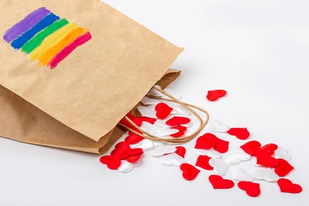 Conjunto de corações de tecido vermelho e branco da sacolinha de papel com a bandeira lgbt de arco-íris pintada na