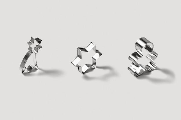 Conjunto de corta-bolachas de aço inoxidável para assar biscoitos caseiros de natal, em forma de estrelas e pão de mel, sobre um fundo cinzento claro com sombras suaves.