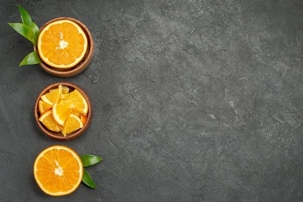Conjunto de corte ao meio fatiado em pedaços, folhas frescas de laranja e flores na mesa preta
