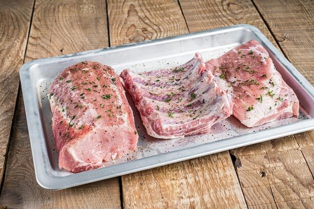 Conjunto de cortes de carne de porco crua, carne de lombo, costela e peito. fundo de madeira. vista do topo.