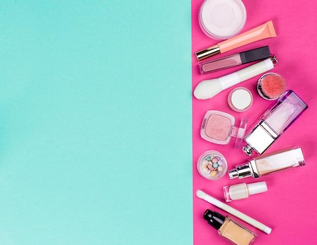 Conjunto de cosméticos coloridos na mesa-de-rosa
