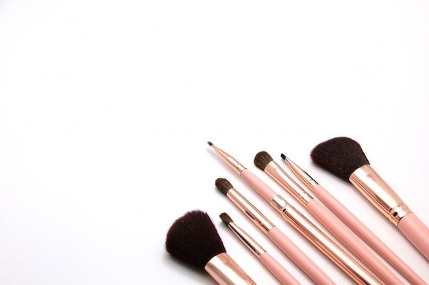 Conjunto de cosméticos de maquiagem pincel na cor rosa flat-lay isolado em um fundo branco