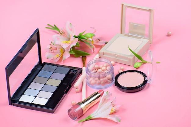 Conjunto de cosméticos decorativos com pincéis de maquiagem em fundo rosa