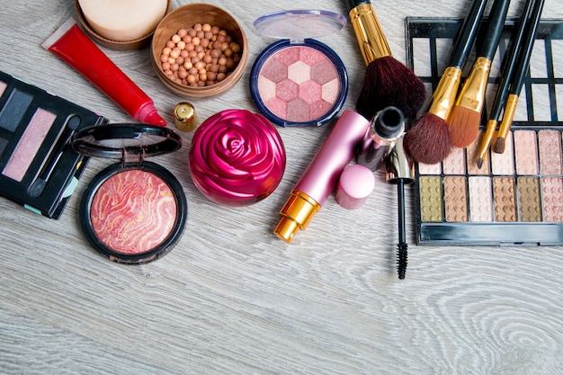 Conjunto de cosméticos decorativos e escovas em fundo cinza de madeira. vários produtos de maquiagem