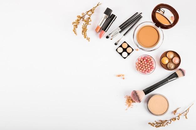 Conjunto de cosméticos decorativos e pincéis de maquiagem em fundo branco