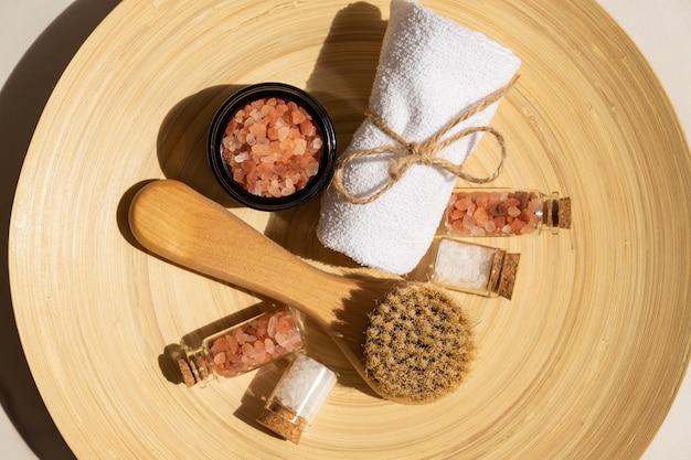 Conjunto de cosméticos naturais em embalagem ecológica em placa de bambu com toalha de algodão e sal marinho. spa, produtos de beleza para banho.
