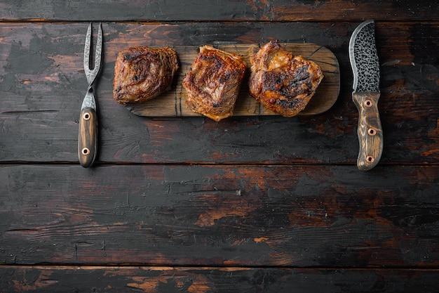 Conjunto de costelas de boi churrasco, na velha mesa de madeira escura