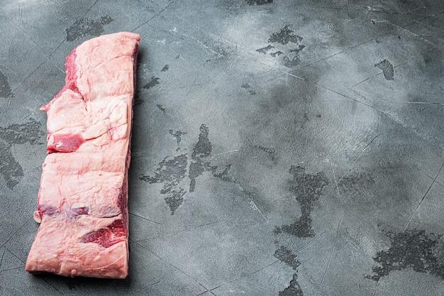 Conjunto de costelas de carne crua orgânica pronta para cozinhar, em mesa de pedra cinza