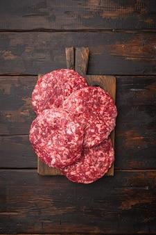 Conjunto de costeleta de carne picada de carne, na velha mesa de madeira escura