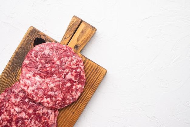 Conjunto de costeletas de hambúrguer de carne crua de carne moída, na pedra branca