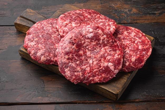 Conjunto de costeletas de hambúrguer de carne crua de carne moída, na velha mesa de madeira escura