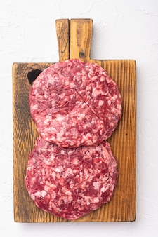Conjunto de costeletas de hambúrgueres de fazendeiros caseiros, picados na hora, em pedra branca