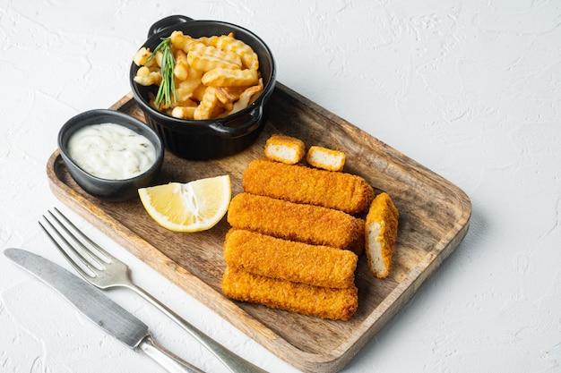 Conjunto de dedos de peixe com batatas fritas, em bandeja de madeira, em fundo branco, com copyspace e espaço para texto
