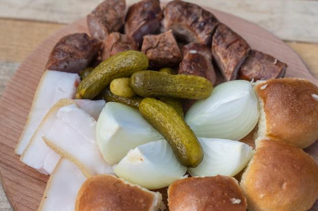 Conjunto de deliciosa comida ucraniana, close-up. pepino, cebola, gordura, pão e linguiça em um prato, vista de cima