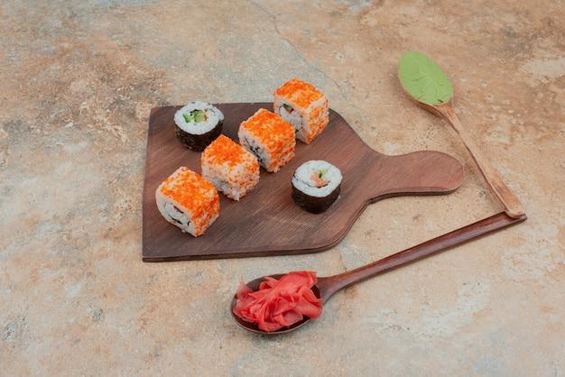 Conjunto de delicioso sushi roll com colher e molho de soja no mármore
