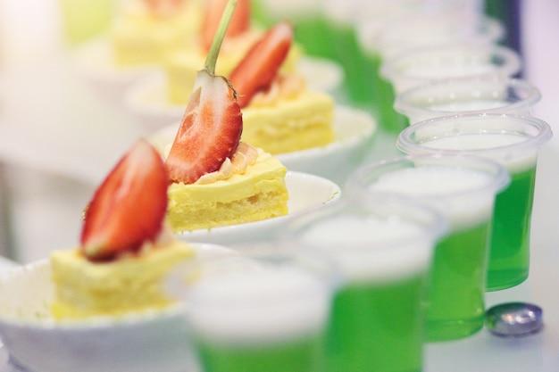 Conjunto de deliciosos canapés com morango e cheesecake