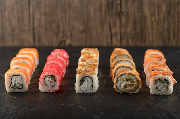Conjunto de deliciosos rolos de sushi tradicionais em superfície preta