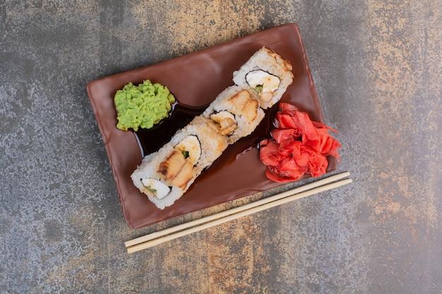 Conjunto de deliciosos sushis com pauzinhos e gengibre em espaço de mármore