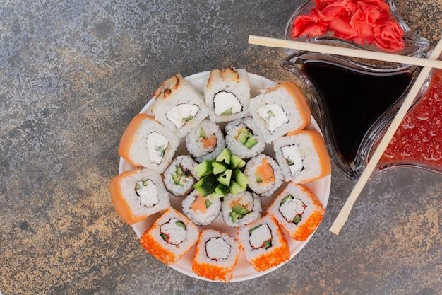 Conjunto de deliciosos sushis com pauzinhos e gengibre em superfície de mármore