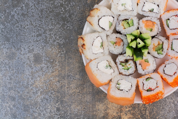 Conjunto de deliciosos sushis diferentes em um prato de madeira
