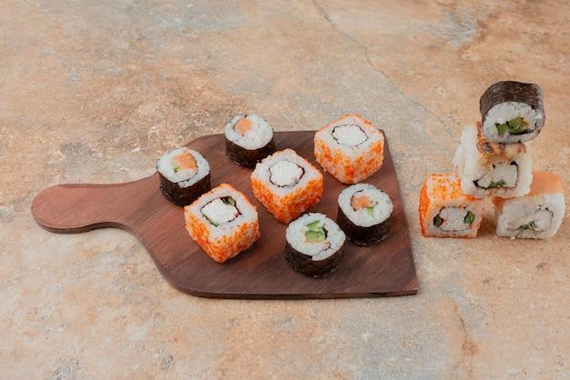 Conjunto de deliciosos sushis no prato de madeira