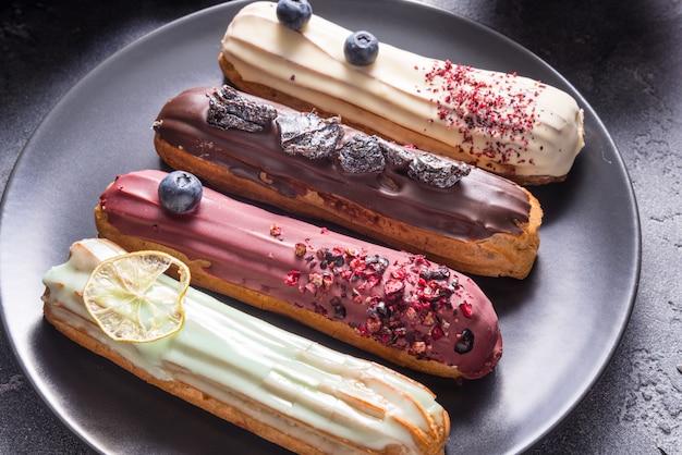 Conjunto de diferentes bolos de eclair em fundos escuros
