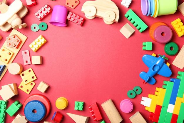 Conjunto de diferentes brinquedos infantis em uma vista superior de fundo colorido