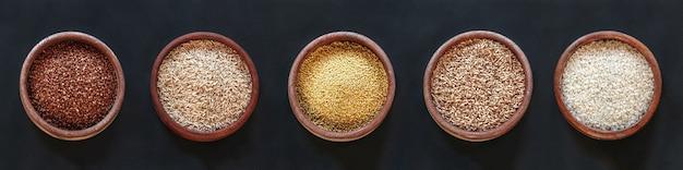 Conjunto de diferentes cereais e arroz em tigelas de madeira em um fundo preto, vista superior