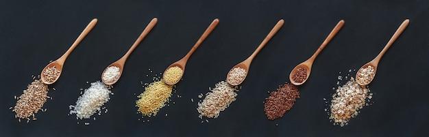 Conjunto de diferentes cereais e arroz na colher de pau em um fundo preto, vista superior