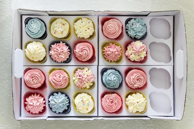 Conjunto de diferentes cupcakes caseiros deliciosos em caixa de entrega de papel.