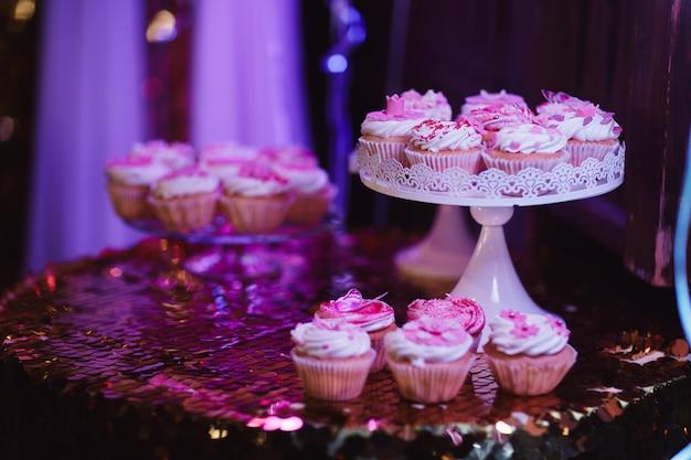 Conjunto de diferentes deliciosos bolos deliciosos no fundo festivo de mesa com toalha de mesa rosa brilhante.