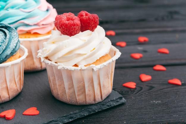 Conjunto de diferentes deliciosos cupcakes no escuro