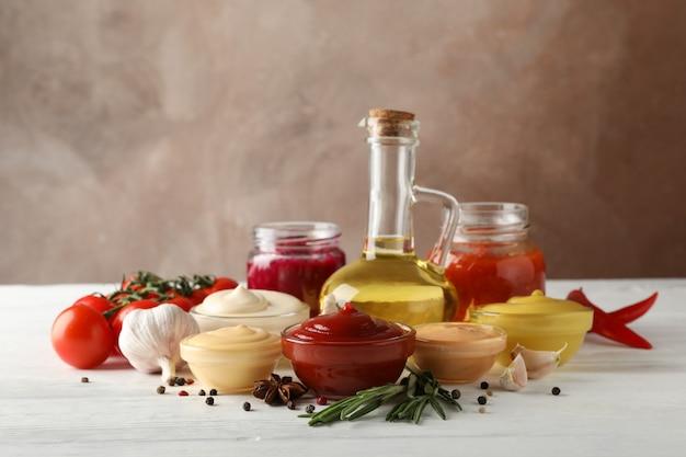 Conjunto de diferentes deliciosos molhos, alho, tomate cereja, azeite de oliva no fundo branco, espaço para texto