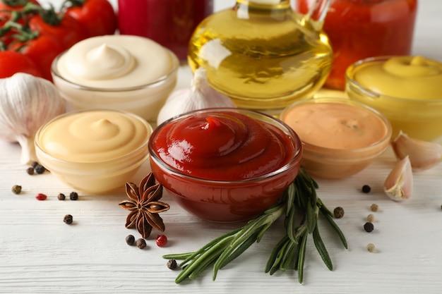 Conjunto de diferentes deliciosos molhos, alho, tomate cereja, azeite em branco