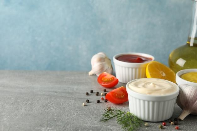 Conjunto de diferentes deliciosos molhos, alho, tomate cereja, limão em fundo cinza, espaço para texto