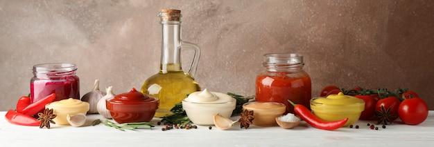 Conjunto de diferentes deliciosos molhos, azeite, alho, tomate cereja na mesa branca contra um fundo marrom, espaço para texto