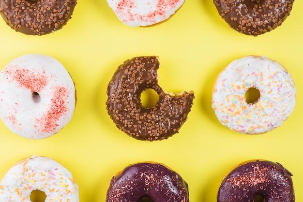 Conjunto de diferentes donuts de geada redonda colorida com marca de mordida
