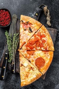 Conjunto de diferentes fatias de pizza. fundo preto. vista do topo.
