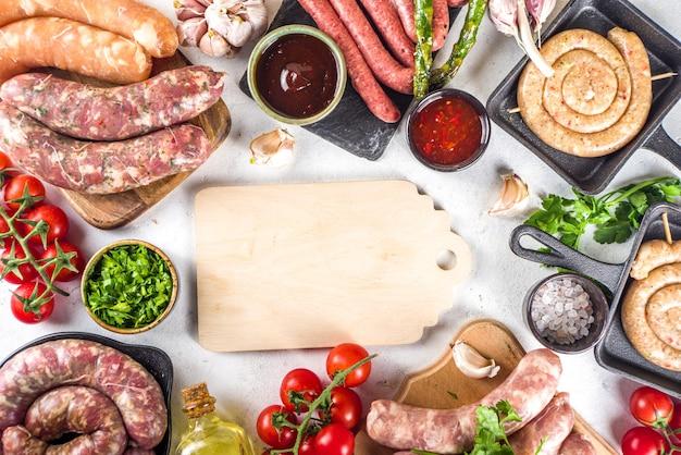 Conjunto de diferentes linguiças de carne crua, carne de porco e frango na mesa de cozimento com especiarias, molhos e vegetais para grelhar.