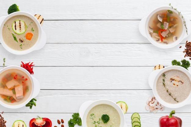 Conjunto de diferentes molduras de sopas apetitosas na mesa de madeira