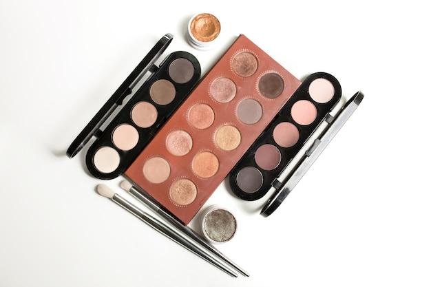 Conjunto de diferentes paletas de sombras e pincéis de maquiagem em um fundo branco