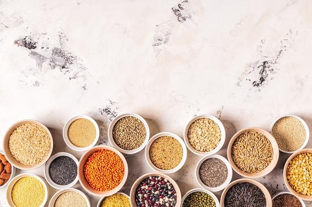 Conjunto de diferentes superalimentos - grãos inteiros, feijão e legumes, sementes e nozes, vista superior.