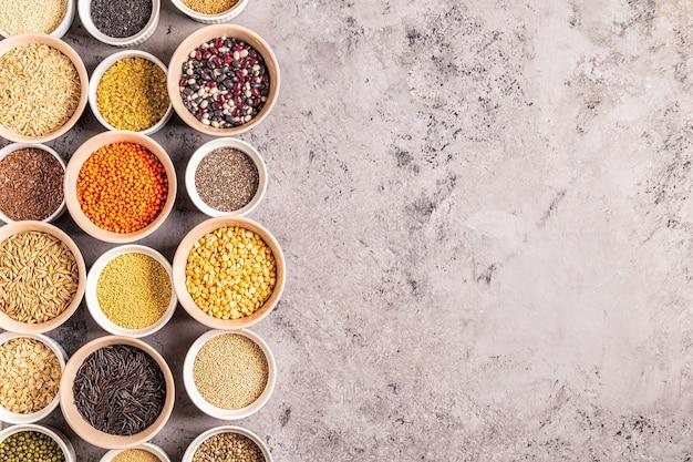 Conjunto de diferentes superalimentos - grãos inteiros, feijão e leguminosas, sementes e nozes, vista superior.