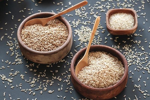 Conjunto de diferentes tipos de arroz e cereais em tigelas de madeira e