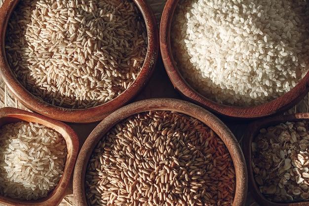 Conjunto de diferentes tipos de arroz e cereais em tigelas de madeira