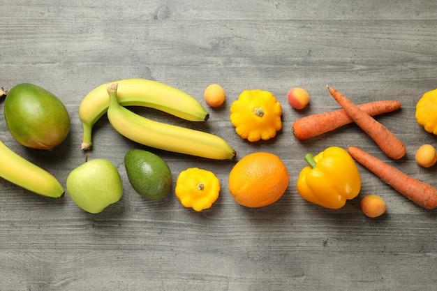 Conjunto de diferentes vegetais e frutas em plano de fundo texturizado cinza
