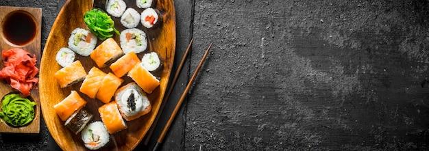 Conjunto de diversos rolos de sushi com gengibre, molho de soja e wasabi. na superfície rústica preta