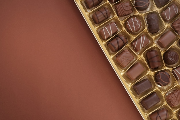 Conjunto de doces de chocolate. caixa de close-up de chocolates. doces de chocolate definidos em uma caixa aberta. top view.sweet dessert closeup